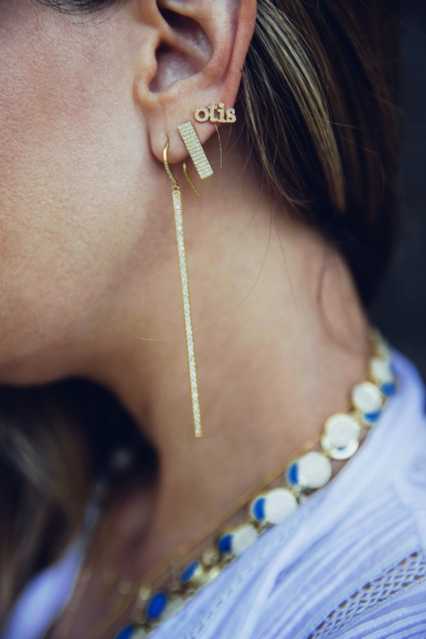 Jennifer wears a custom earring for her son Otis with the long stick and rectangular stud earrings.